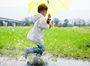 黄色い傘をさして走る男の子の写真素材 [FYI01868873]