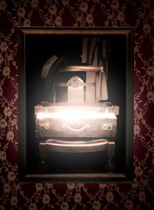 光が漏れる椅子の上のトランクの写真素材 [FYI01869482]