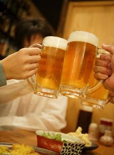 乾杯でぶつかりあうビールグラスの写真素材 [FYI01869576]