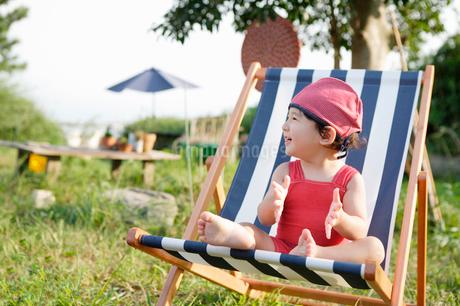 デッキチェアに座って手を叩いて喜ぶ男の子の写真素材 [FYI01869720]