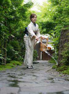 打ち水をする着物姿の女性の写真素材 [FYI01869915]