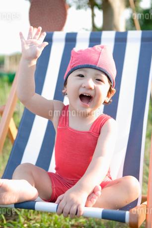 デッキチェアに座って手を上げている男の子の写真素材 [FYI01870096]