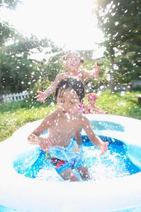 水しぶきを上げて庭のプールで遊ぶ三人の姉弟の写真素材 [FYI01870496]