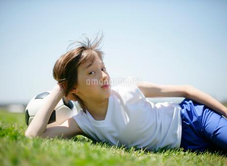 芝生の上で休憩しているサッカー少年の写真素材 [FYI01870507]