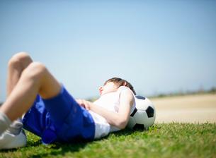 芝生の上に横になっているサッカー少年の写真素材 [FYI01870829]