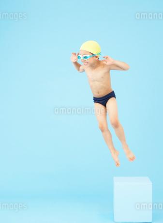 飛び込み台からジャンプする男の子の写真素材 [FYI01871045]