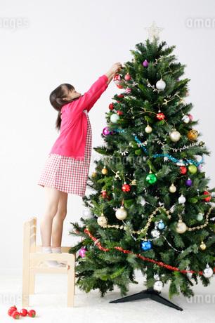 クリスマスツリーの飾り付けをする女の子の写真素材 [FYI01871358]