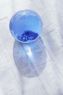 英字新聞の上のガラスの地球儀の写真素材 [FYI01871825]