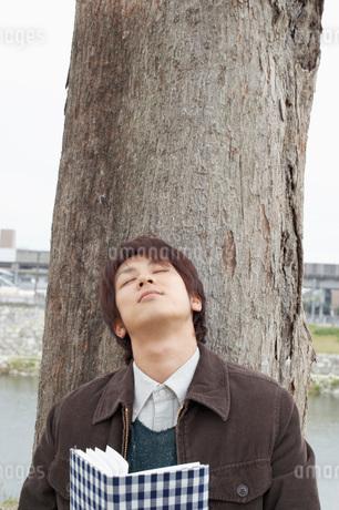 木にもたれて目を閉じる男性の写真素材 [FYI01871901]