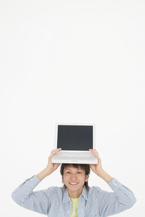 ノートパソコンを頭にのせた男性の写真素材 [FYI01872067]