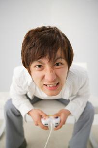 ゲームに熱中するしかめっ面の男性の写真素材 [FYI01872566]