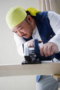 電動のこぎりで木を切る男性の写真素材 [FYI01872584]