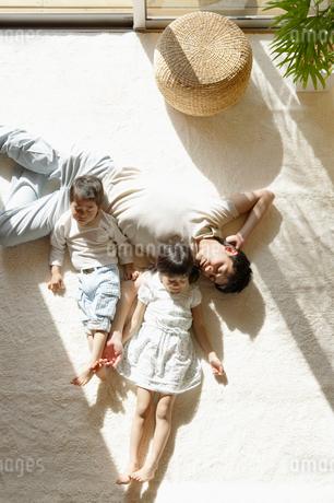 リビングで寝転ぶ日本人家族の写真素材 [FYI01873693]