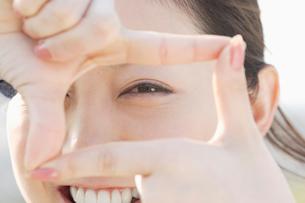 フレームの中から覗く日本人女性の目のアップの写真素材 [FYI01873717]