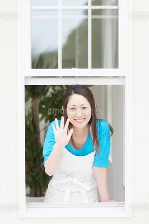 窓から手を振る女性の写真素材 [FYI01873727]
