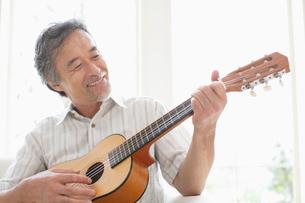 ギターを弾く中高年の男性の写真素材 [FYI01874570]