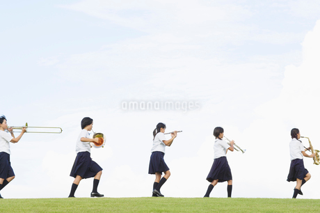 楽器を演奏しながら歩く女子中学生の写真素材 [FYI01876011]