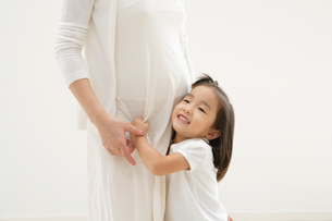 妊婦の母親に抱き着く女の子の写真素材 [FYI01876742]