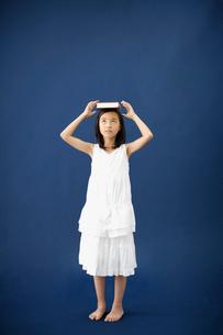 本を頭に乗せる女の子の写真素材 [FYI01876922]