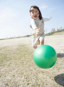 野原でボールを追いかける女の子の写真素材 [FYI01876932]