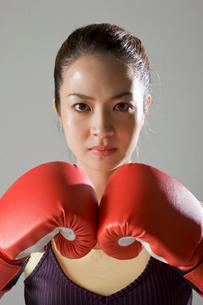 ボクシンググローブをつけて構える女性の写真素材 [FYI01881672]