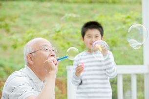シャボン玉で遊ぶ祖父と孫の写真素材 [FYI01882296]
