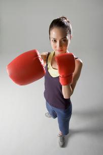 ボクシンググローブをつけて構える女性の写真素材 [FYI01882303]