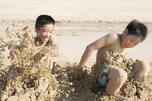 砂遊びをする二人の少年の写真素材 [FYI01883126]