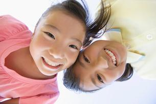 笑顔で覗き込む二人の少女の写真素材 [FYI01883579]