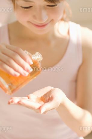 マッサージオイルを手にとる女性の写真素材 [FYI01884084]