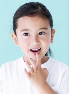 唇に手をあてる女の子の写真素材 [FYI01884524]
