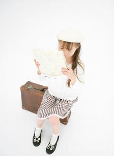 トランクに腰掛け地図を見る女の子の写真素材 [FYI01885079]