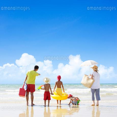 波打ち際に立つ家族の写真素材 [FYI01885221]