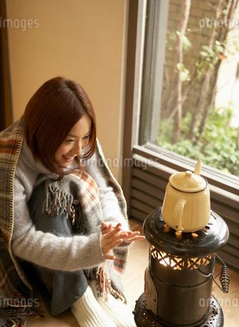 ストーブの前で暖まる女性の写真素材 [FYI01885269]