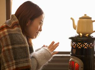 ストーブの前で暖まる女性の写真素材 [FYI01885276]