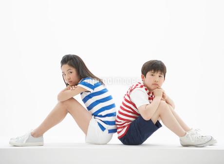 背中合わせをして座る男の子と女の子の写真素材 [FYI01886253]