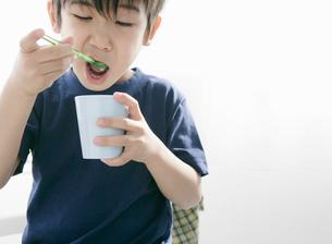 飲み物のコップを片手にスプーンをなめる少年の写真素材 [FYI01886519]