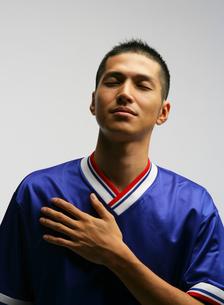 胸に手をあてるサッカーのユニフォームを着た男性の写真素材 [FYI01886612]