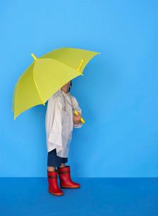 黄色い傘をさす男の子の写真素材 [FYI01886952]