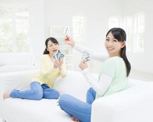 ソファに座ってトランプをする二人の女性の写真素材 [FYI01887387]