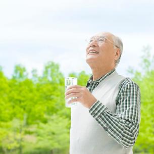 グラスを持って見上げるシニア男性の写真素材 [FYI01887709]