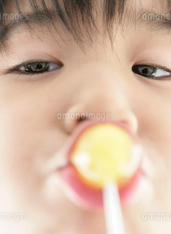 棒つきキャンディを口にする少年の写真素材 [FYI01887933]