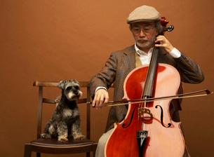 チェロを弾く男性とミニチュアシュナウザーの写真素材 [FYI01888033]