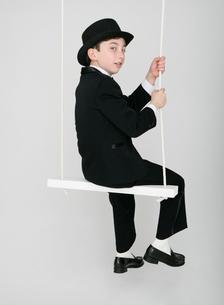 ブランコに乗る正装した少年の写真素材 [FYI01888709]