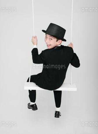 ブランコに乗る正装した少年の写真素材 [FYI01889206]