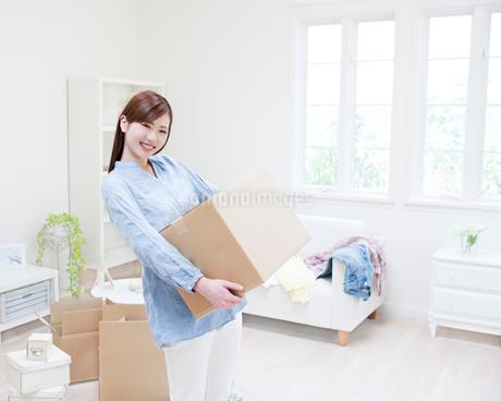 段ボール箱を抱える女性の写真素材 [FYI01889696]