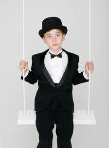 ブランコに乗る正装した少年の写真素材 [FYI01890014]