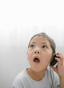 ヘッドホーンを耳にあてる子供の写真素材 [FYI01890230]
