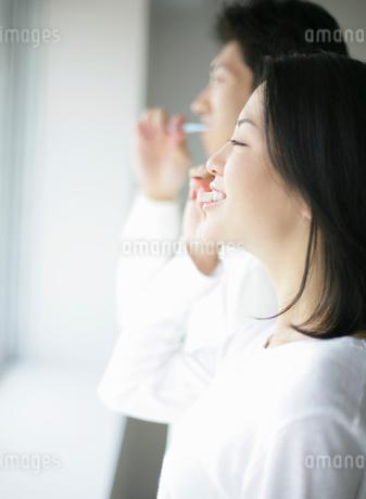 窓辺で歯を磨くカップルの写真素材 [FYI01890319]