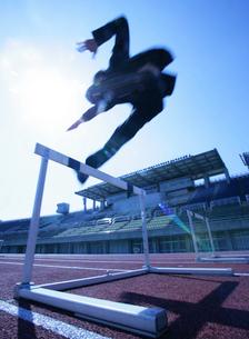 ハードルを飛び越えるビジネスマンの写真素材 [FYI01890699]